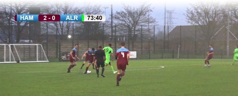 Footballers at the Dorset FA pitch at Hamworthy FC play under a custom scoreboard