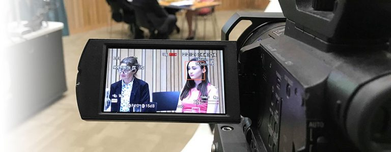 Two participants sit at a table on camera at the Family Law Symposium at Bournemouth University